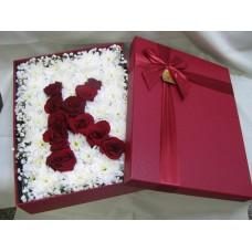 Буква от рози аранжирани в кутия.