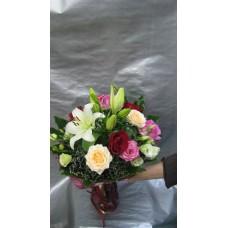 Пъстроцветен букет с лилиум, рози и еустома, аранжиран с листа аспидистра , аралия и гипсофил