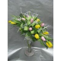 Букет с жълти и розови лалета аранжиран с нежна зеленина,, листа аспедистра и бели клони