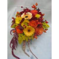 Слънчев есенен букет с рози, гербер, хризантема, солидаго и амарантос аранжиран с клонки шипка и есенни листа